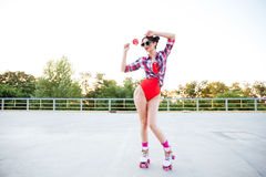 Beautiful young woman holding lollipop and standing on roller skates Royalty Free Stock Images
