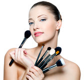 Beautiful Young Woman Holding Make-up Brushes Royalty Free Stock Photo
