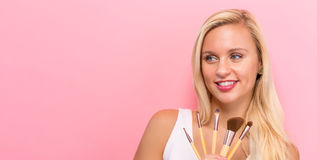 Beautiful young woman holding makeup brushes Royalty Free Stock Image