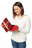 Beautiful young woman holding an open gift box and looking at the present. Royalty Free Stock Photos