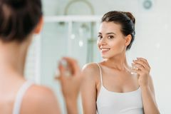Beautiful young woman holding perfume bottle and looking at mirror. In bathroom stock photography