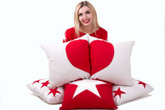 Beautiful young woman holding a pillow with the heart. Beautiful pillows to decorate the interior of the house. Pillow with star o. Beautiful pillows to decorate stock photos