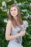 Beautiful young woman holding pink lilac flower Stock Photo