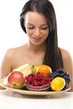 Beautiful young woman holding a plate with fresh fruit Royalty Free Stock Photography