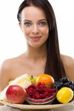Beautiful young woman holding a plate with fresh fruit Stock Photo
