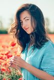 Beautiful young woman with poppy flower. Beautiful young woman holding poppy flower and looking at camera in spring meadow outdoor stock photography
