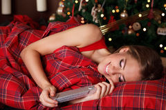 Beautiful young woman holding a present in the bed Stock Photography