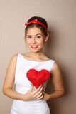 Beautiful young woman holding a red heart Royalty Free Stock Images