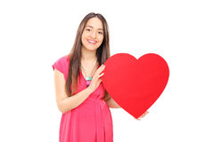 Beautiful young woman holding a red heart Royalty Free Stock Photos