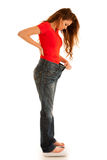 Beautiful young woman holding scale and too big trousers as she Royalty Free Stock Photography