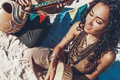 Beautiful young woman holding shaman drum and playing ethnical music royalty free stock photography