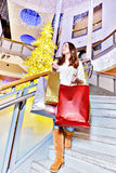 Beautiful young woman holding shopping bags. Beautiful young woman in white knitted sweater and blue jeans posing with shopping bags in mall during the Christmas Stock Photos