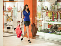 Beautiful young woman holding shopping bags walking in the shop Stock Photography