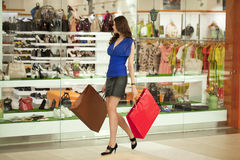 Beautiful young woman holding shopping bags walking in the shop Royalty Free Stock Photo