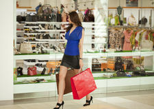 Beautiful young woman holding shopping bags walking in the shop Royalty Free Stock Image