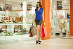 Beautiful young woman holding shopping bags walking in the shop Stock Photos