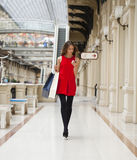 Beautiful young woman holding shopping bags walking in the shop Stock Images
