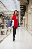 Beautiful young woman holding shopping bags walking in the shop Royalty Free Stock Photography