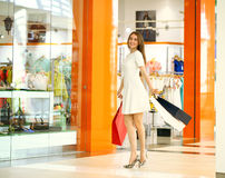 Beautiful young woman holding shopping bags walking in the shop Royalty Free Stock Photos