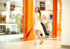 Beautiful young woman holding shopping bags walking in the shop Stock Image