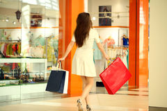 Beautiful young woman holding shopping bags walking in the shop Stock Photo