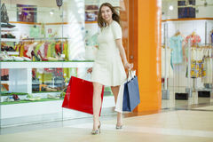Beautiful young woman holding shopping bags walking in the shop Stock Photo