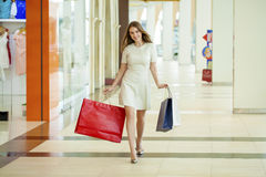 Beautiful young woman holding shopping bags walking in the shop Royalty Free Stock Images