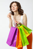 Beautiful young woman holding shopping paper bags and painting h Royalty Free Stock Photos