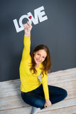 Beautiful young woman is holding a sign with the word: love Royalty Free Stock Image