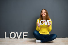 Beautiful young woman is holding a sign with the word: love Royalty Free Stock Photo
