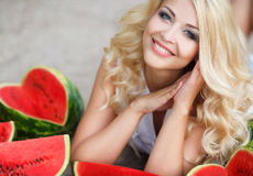Beautiful young woman holding a slice of ripe watermelon. Beautiful blonde model looks with long curly hair and grey eyes,dressed in a white blouse,light makeup stock photo