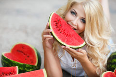 Beautiful young woman holding a slice of ripe watermelon. Beautiful blonde model looks with long curly hair and grey eyes,dressed in a white blouse,light makeup royalty free stock images