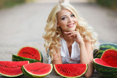 Beautiful young woman holding a slice of ripe watermelon. Beautiful blonde model looks with long curly hair and grey eyes,dressed in a white blouse,light makeup stock image