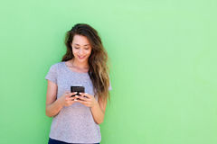 Beautiful young woman holding smart phone on green background Stock Photos