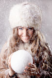 Beautiful young woman holding a snow ball Stock Photography
