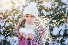 Beautiful young woman holding a snow and blowing on it Royalty Free Stock Photos
