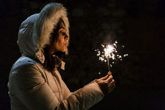 Beautiful young woman holding a sparkle at night, having fun and Royalty Free Stock Images