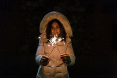 Beautiful young woman holding a sparkle at night, having fun and Stock Image