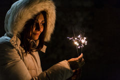 Beautiful young woman holding a sparkle at night, having fun and Stock Photos
