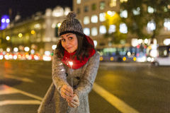 Beautiful young woman holding a sparkle at night, having fun and Stock Photography