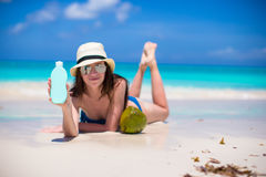 Beautiful young woman holding a suncream lying on tropical beach Stock Image