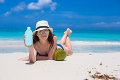 Beautiful young woman holding a suncream lying on Stock Images