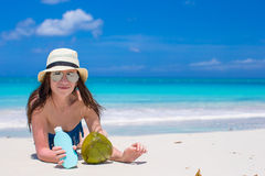 Beautiful young woman holding a suncream lying on Stock Image