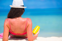 Beautiful young woman holding a suncream lying on Royalty Free Stock Photography