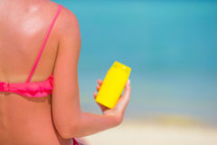 Beautiful young woman holding a suncream lying on Royalty Free Stock Image