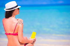 Beautiful young woman holding a suncream lying on Stock Photography