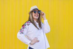 Beautiful young woman holding sunglasses and smiling. Yellow background Royalty Free Stock Photo
