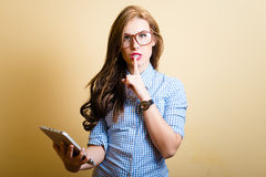 Beautiful young woman holding tablet pc showing. Picture of beautiful young woman holding tablet pc with her finger on lips showing silence sign Royalty Free Stock Images
