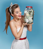 Beautiful young woman holding a transparent jar full of american dollars and happy smiling. Shopping concept Royalty Free Stock Photography