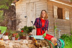 Beautiful young woman potting plants in the garden royalty free stock photos
